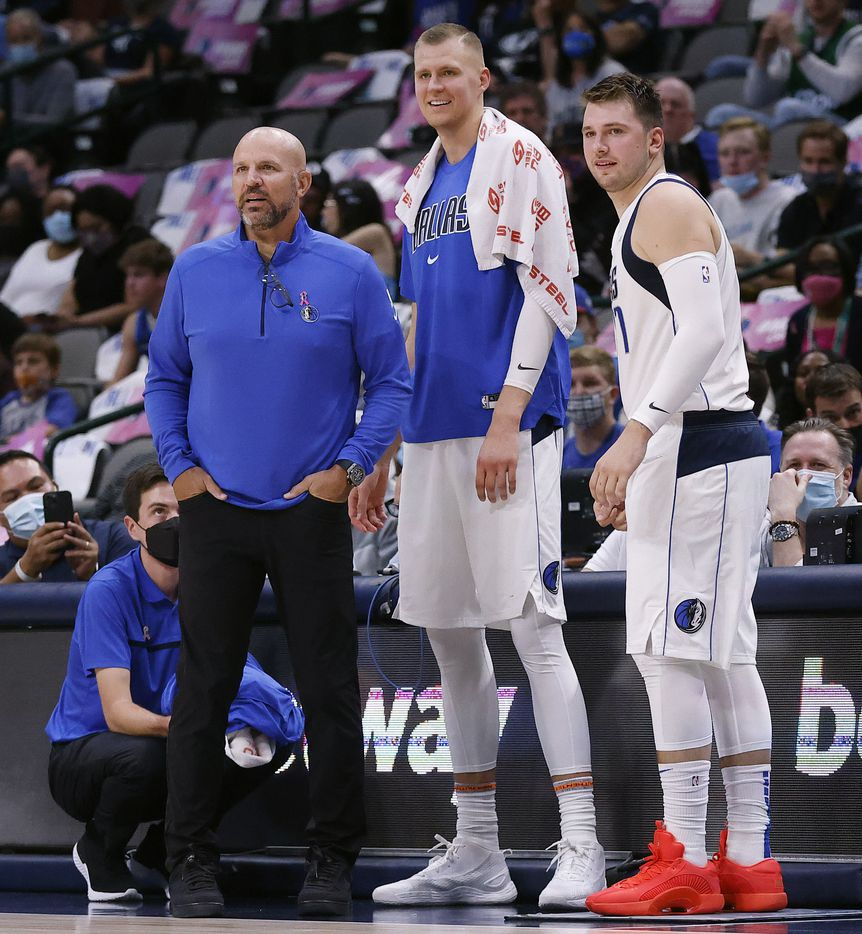 Dallas Mavericks head coach Jason Kidd, center Kristaps Porzingis (center) and guard Luka Doncic watch from the scorers table as the team competes against the Utah Jazz in the first half at the American Airlines Center in Dallas, Wednesday, October 6, 2021.(Tom Fox/The Dallas Morning News)