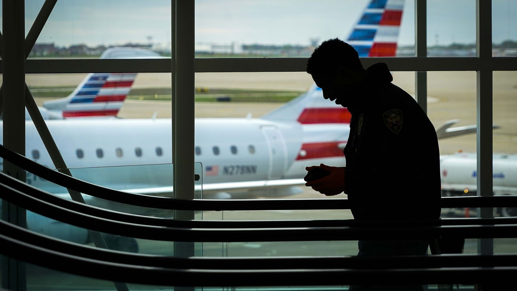 American Airlines are planes parked at their gates as passengers ride an escalator at DFW International Airport Terminal B on March 20.