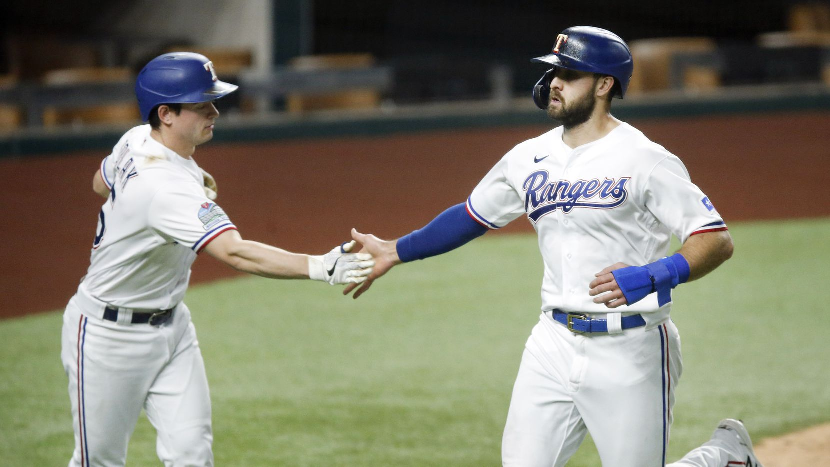 Texas Rangers Joey Gallo (right) is congratulated by teammate Nick Solak after they both scored on a Los Angeles Angels error during the fourth inning at Globe Life Field in Arlington, Texas, Tuesday, September 8, 2020.