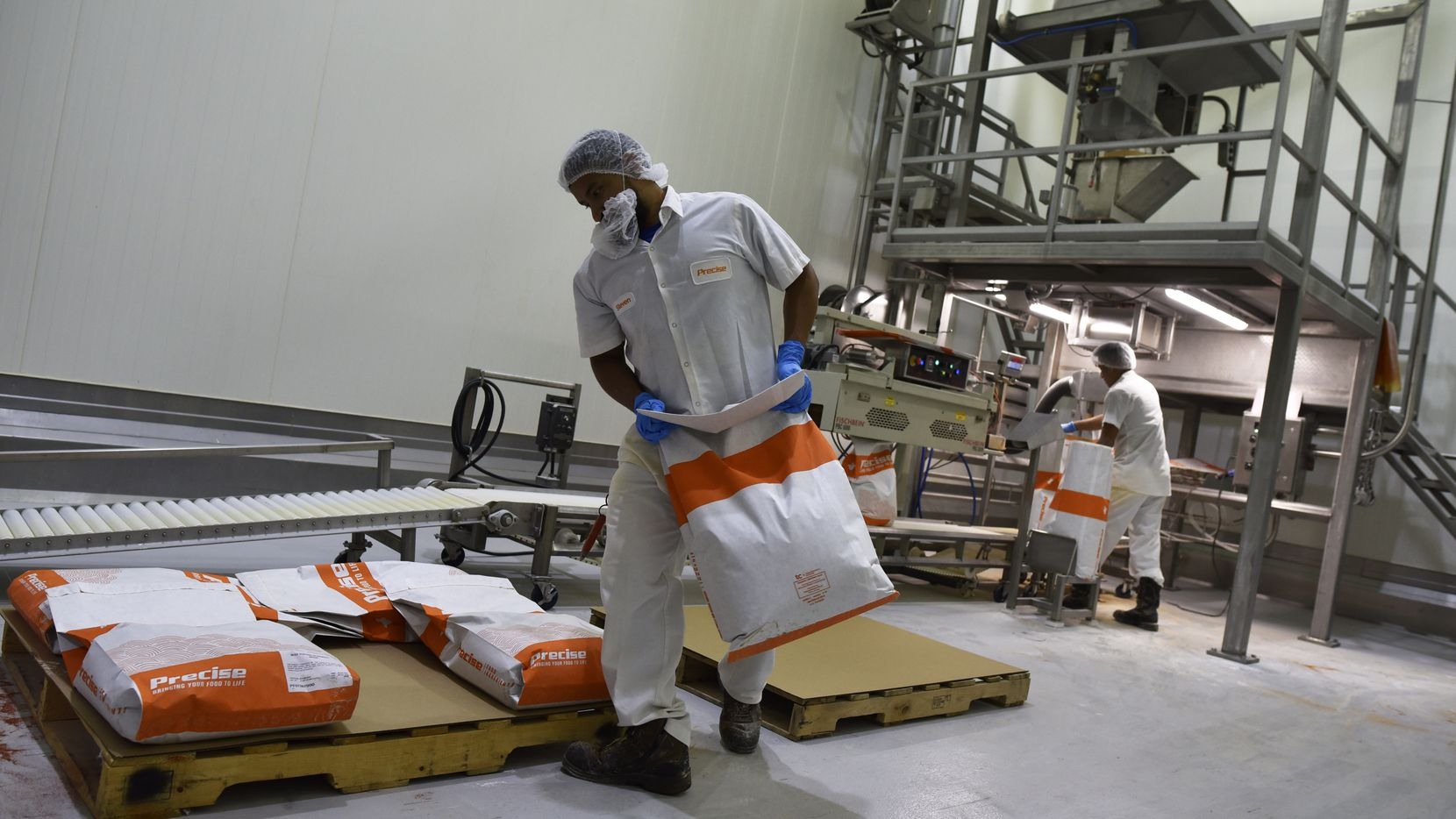 Packaging operators Steven Gallego, left, and Xavier Meza, packed beef topping seasoning inside one of the warehouses of Precise Food Ingredients in Carrollton in 2019.