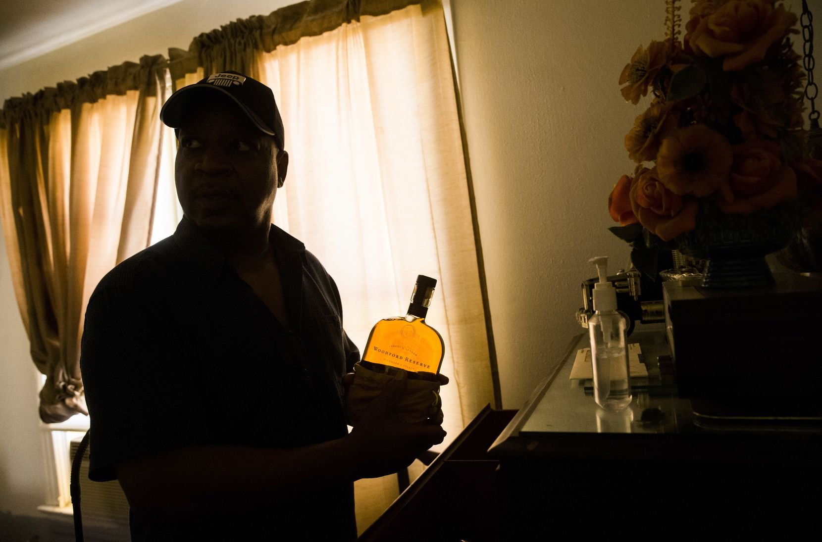 Martin Wilford, a relative of Richard Overton, pulls one of his cousin's whiskey bottles from a dresser drawer. Overton has them stashed all over the house, especially after receiving more than 40 for his 111th birthday.  (Ashley Landis/Staff Photographer)