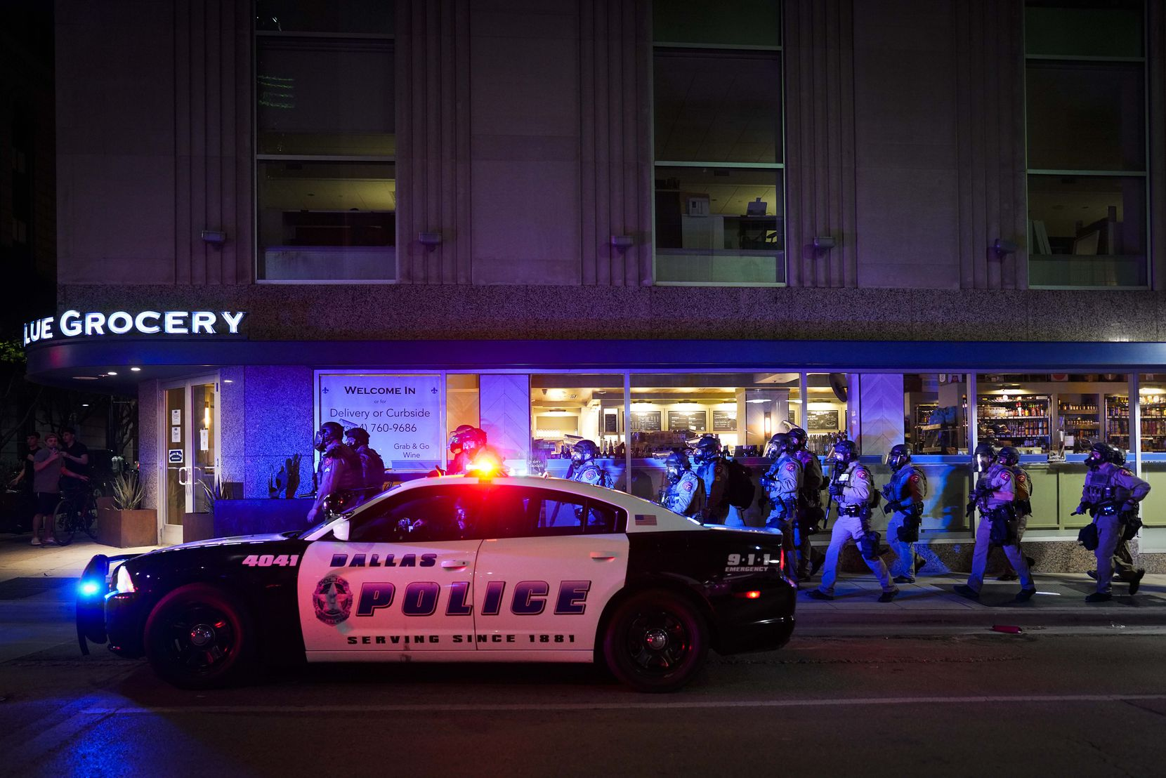 A group of Texas Department of Public Safety troopers moves up Ervay Street as they work to clear groups of people from downtown streets following a protest against police brutality in the early morning hours of Saturday, May 30, 2020, in Dallas.