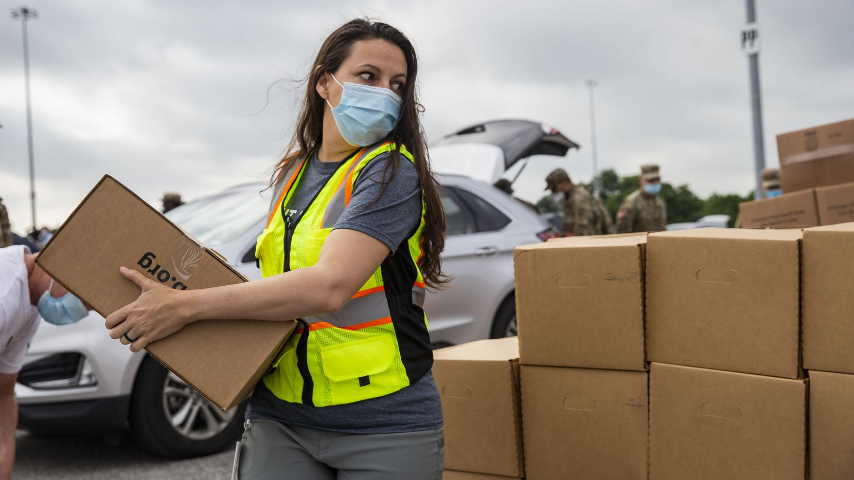 Dr. Valerie Hawthorne, government relations director for the North Texas Food Bank, helps moved boxes of snack packs at Fair Park on Thursday.