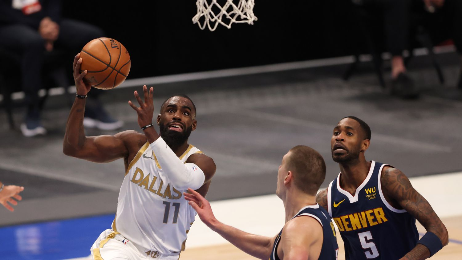 Dallas Mavericks forward Tim Hardaway Jr. (11) attempts a layup in front of Denver Nuggets center Nikola Jokic (15) and Denver Nuggets forward Will Barton III (5) during the first quarter of play at American Airlines Center on Monday, January 25, 2021in Dallas.