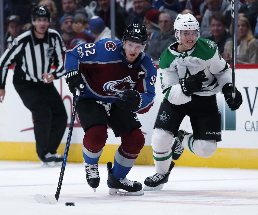 Colorado Avalanche left wing Gabriel Landeskog, left, of Sweden, drives down the ice with the puck as Dallas Stars defenseman Julius Honka, of Finland, pursues in the third period of an NHL hockey game Tuesday, Oct. 24, 2017, in Denver. The Avalanche won 5-3. (AP Photo/David Zalubowski)