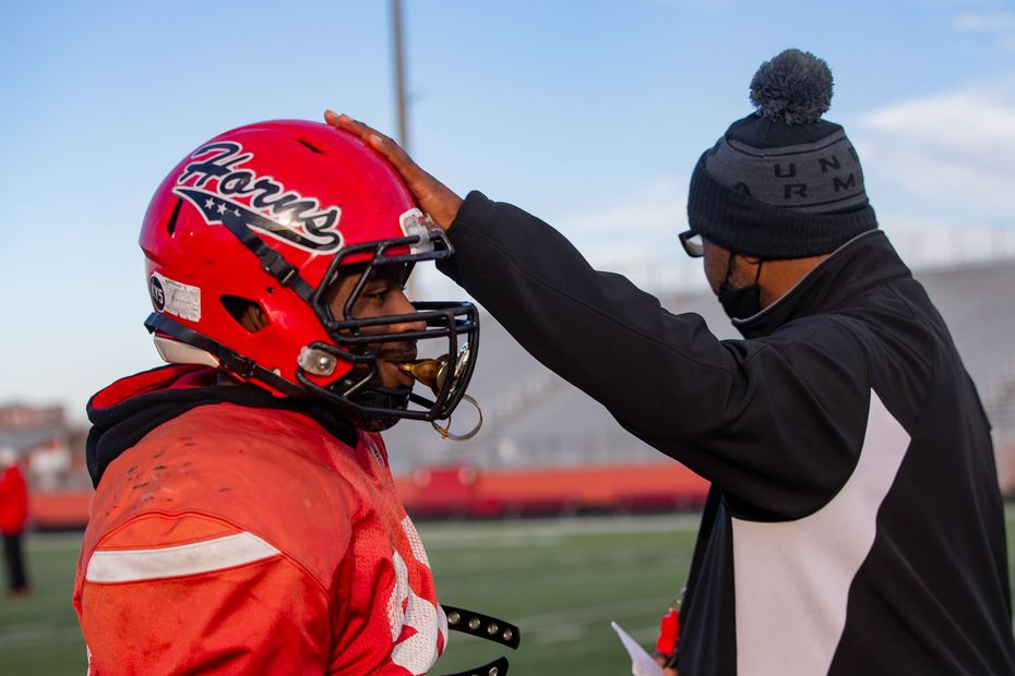 Cedar Hill coach Carlos Lynn touches Kavonte Johnson's (38) helmet during practice at Longhorn Stadium in Cedar Hill on Tuesday, Jan. 12, 2021.