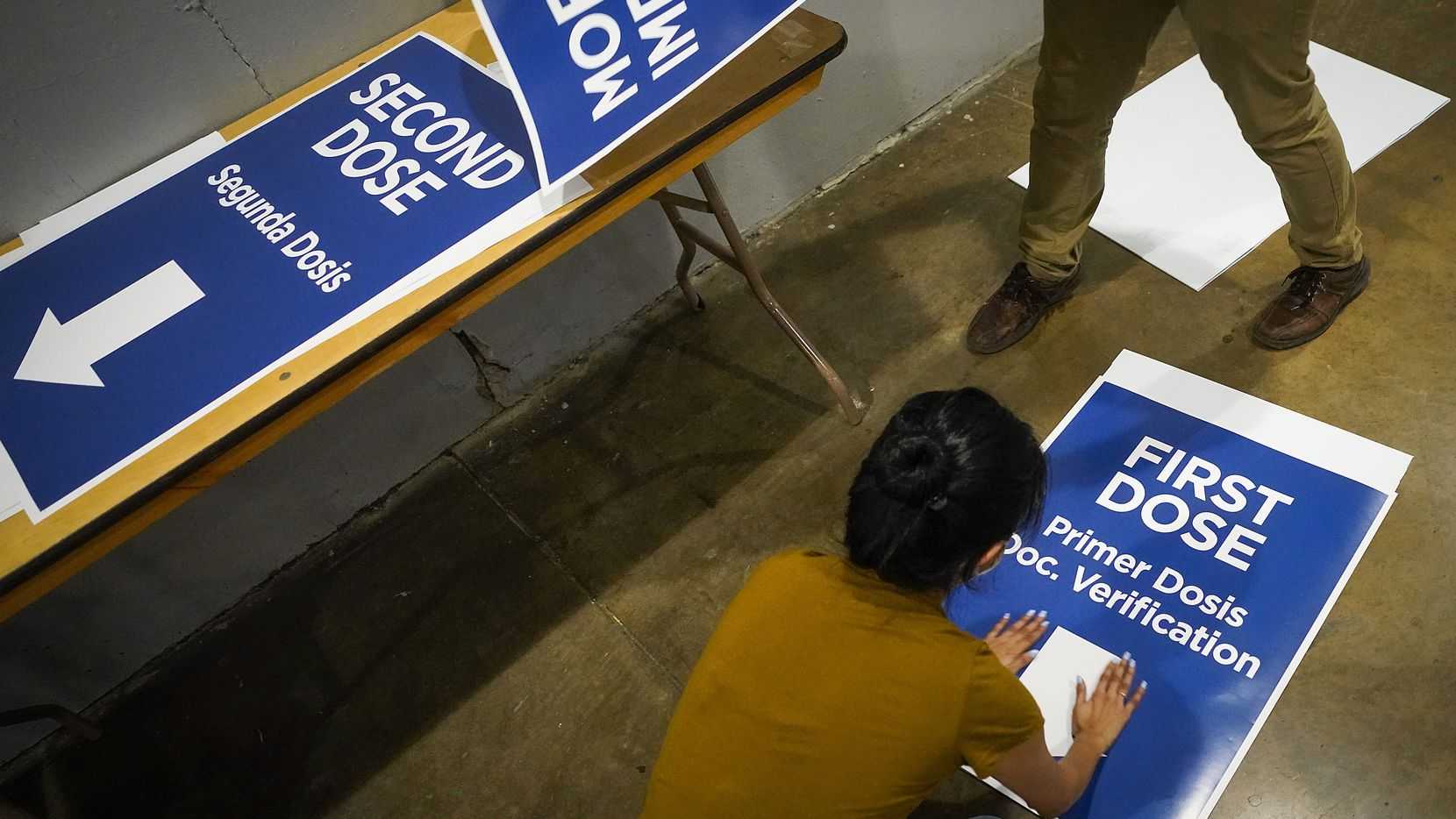 Workers prepare signs that will direct lines of people receiving either their first of second doses of vaccine at the Dallas County COVID-19 vaccination megasite at Fair Park on Friday, Jan. 22, 2021, in Dallas.