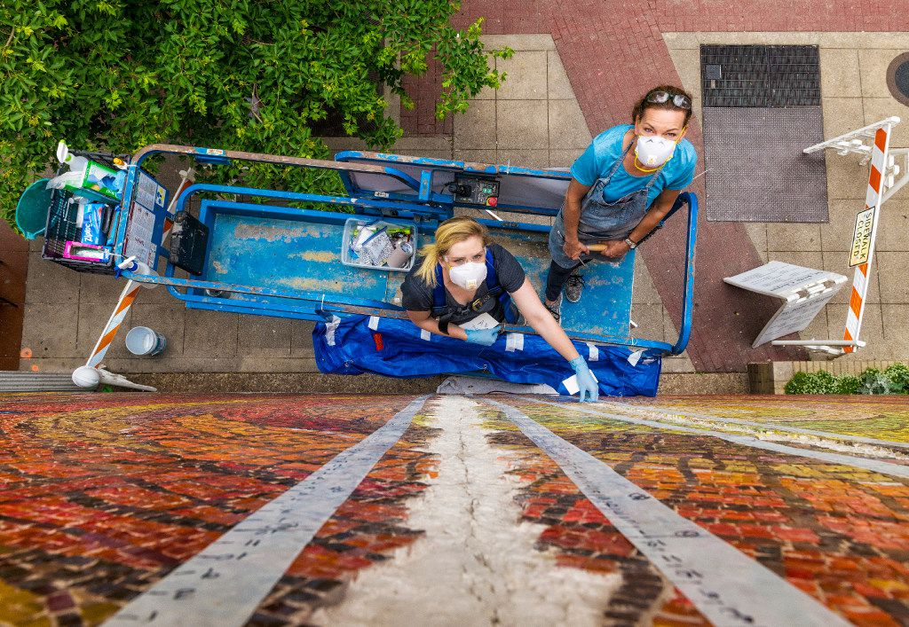 Callie Heimburger and Julie Richey work to remove cracked mortar, reinforce the gap and apply an anti-fracture membrane to the exterior mosaic at St. Jude Catholic Chapel in downtown Dallas. Credit: Danny Fulgencio