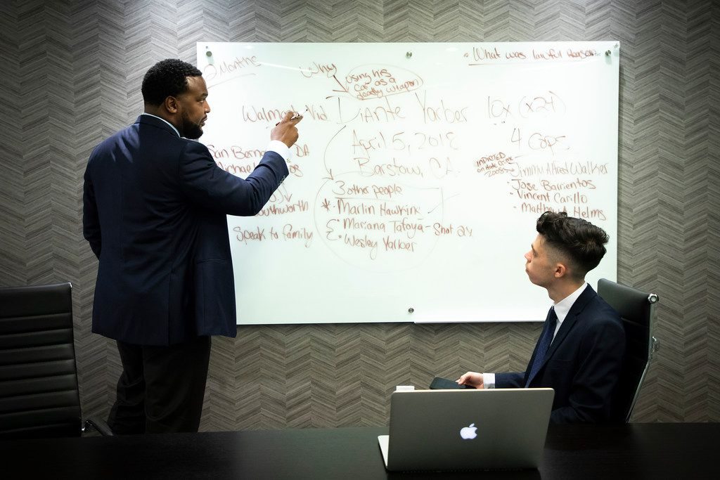 Lee Merritt (left) talks strategy in the case of Diante Yarber with intern Blerim Elmazi, a third-year law student at SMU, in Merritt's downtown Dallas law office. Yarber, a  black man, was unarmed when he was shot 10 times by police in Barstow, Calif., in April.