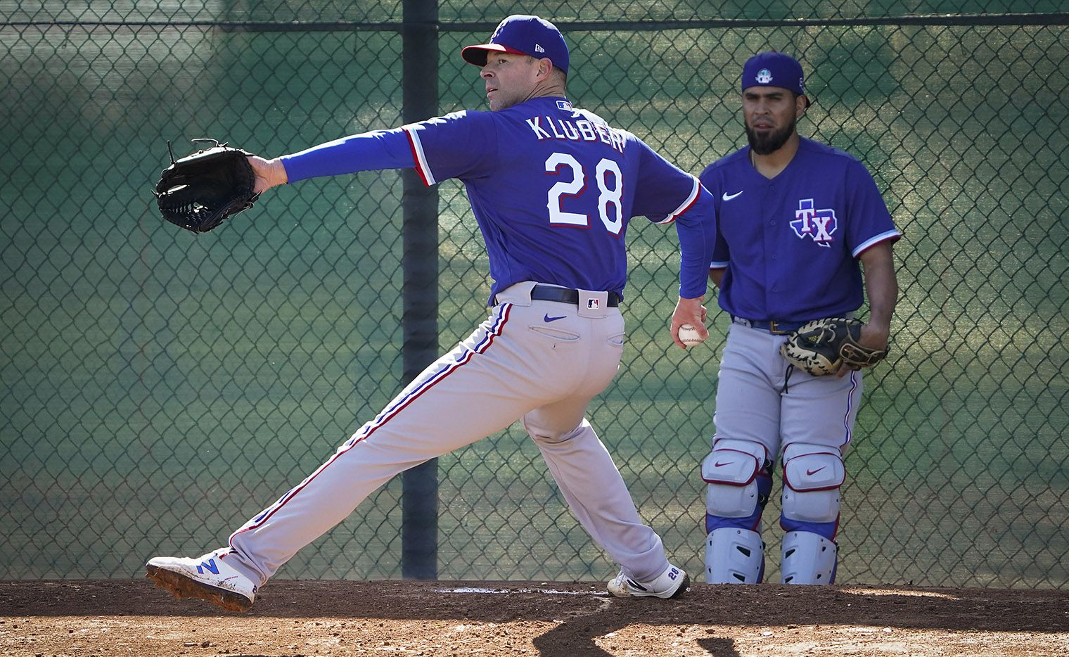 Texas Rangers pitcher Corey Kluber throws in the bullpen as catcher Robinson Chirinos looks on during the first spring training workout for pitchers and catchers at the team's training facility on Wednesday, Feb. 12, 2020, in Surprise, Ariz