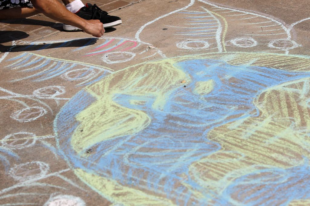 Kevin Sourivong uses sidewalk chalk to draw a picture of the Earth with flower petals surrounding it during Oak Cliff Cultural Center's fourth anniversary block party in August 2014. Irving's Chalk the Block is calling for similarly colorful summer scenes to be colored around the city this weekend.