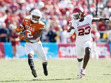 Texas Longhorns quarterback Roschon Johnson (2) runs up the field as Oklahoma Sooners linebacker DaShaun White (23) closes in on him during the second half of play in the Red River Showdown at the Cotton Bowl in Dallas on Saturday, October 12, 2019. Oklahoma Sooners defeated Texas Longhorns 34-27. (Vernon Bryant/The Dallas Morning News)