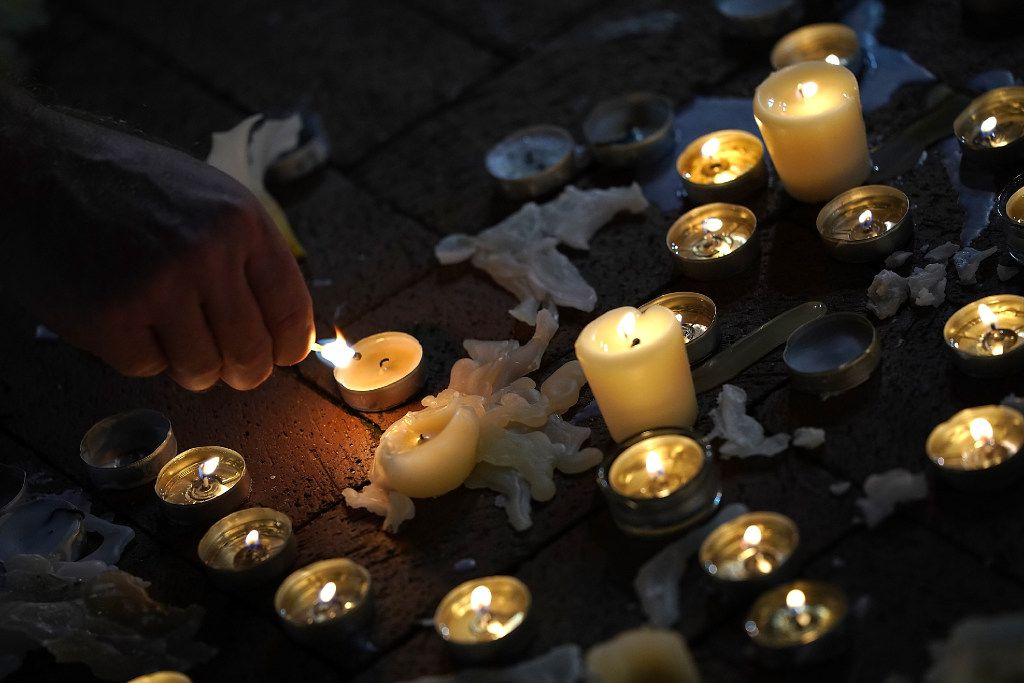 CHARLOTTESVILLE, VA - AUGUST 12:  A man tends a makeshift candlelight vigil for those who died and were injured when a car plowed into a crowd of anti-fascist counter-demonstrators marching near a downtown shopping area August 12, 2017 in Charlottesville, Virginia. The car allegedly plowed through a crowd, and at least one person has died from the incident, following the shutdown of the 'Unite the Right' rally by police after white nationalists, neo-Nazis and members of the 'alt-right' and counter-protesters clashed near Lee Park, where a statue of Confederate General Robert E. Lee is slated to be removed.  (Photo by Win McNamee/Getty Images)