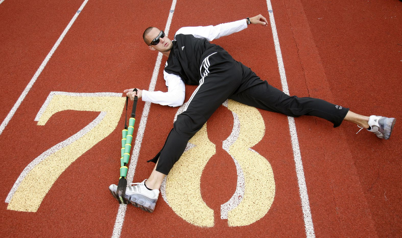 From 2007: Jeremy Wariner stretches before working out at the Baylor University Hart-Patterson Track and Field Complex, Texas Monday April 9, 2007.  He is preparing for the 2008 Summer Olympics in Beijing, China.