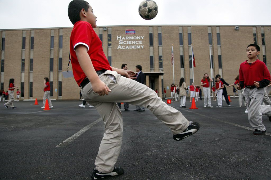 Fourth-grader Hayner Rodriguez plays soccer with his classmates on the blacktop parking lot outside of the Harmony Science Academy in Grand Prairie, a school that's part of a network of charter schools across Texas. (Tom Fox/The Dallas Morning News)