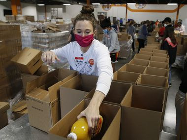 Volunteer Heather Rey of Plano works on filling boxes for a food distribution at North Texas Food Bank on Friday, December 11, 2020 in Plano, Texas. (Vernon Bryant/The Dallas Morning News)