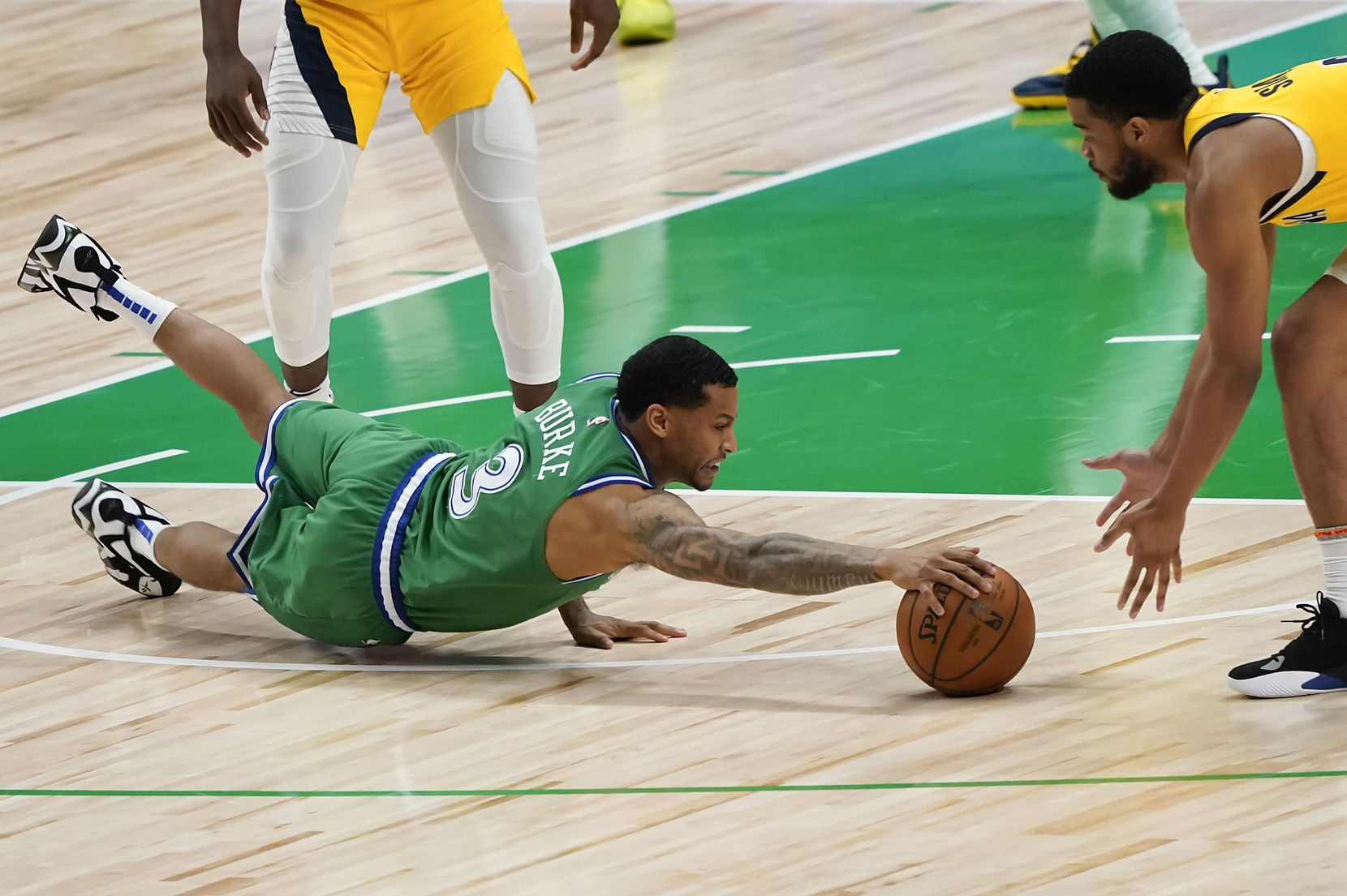 Dallas Mavericks guard Trey Burke (3) dives for a loos ball against Indiana Pacers guard Cassius Stanley during the second half of an NBA basketball game at American Airlines Center on Friday, March 26, 2021, in Dallas.