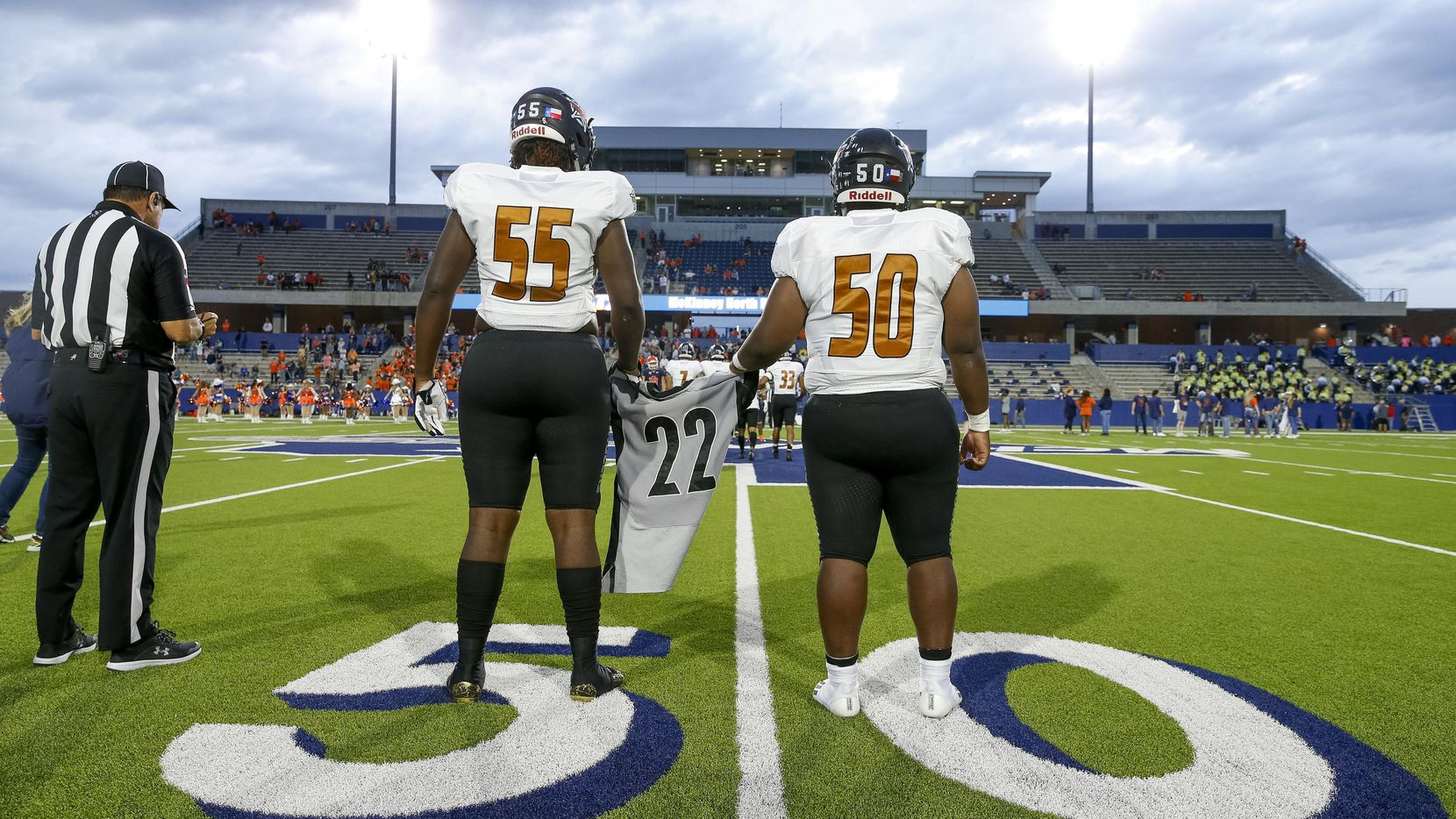 West Mesquite's Donovan Hawthorne (50) and Trey Mitchell (55) hold a number 22 jersey in honor of former West Mesquite football player Aaron Lowe before a game against McKinney North at McKinney ISD Stadium on Thursday, Sept. 30, 2021, in Mckinney, Texas. Lowe was shot and killed on Sept. 26 in Salt Lake City, Utah. Lowe attended the University of Utah and played defensive back for the Utes. (Elias Valverde II/The Dallas Morning News)
