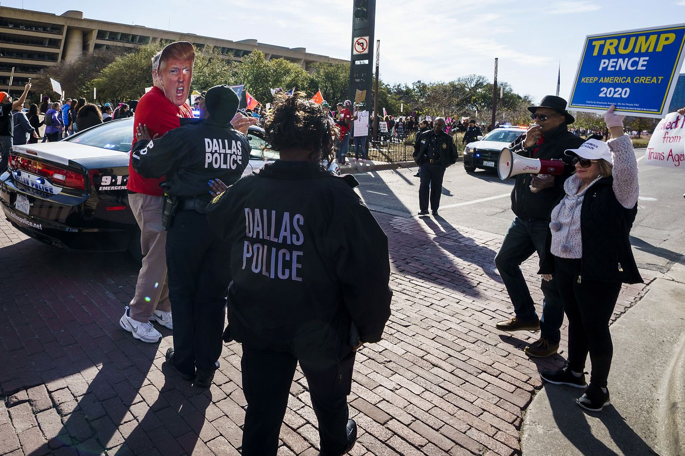 Dallas police separate a participant in the 2020 Dallas Women's March (left, wearing a Trump mask) from a group of Trump supporters (right) who were counter-protesting near Dallas City Hall on Sunday, Jan. 19, 2020, in Dallas.