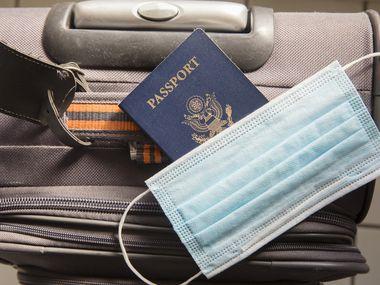Un pasaporte de Estados Unidos junto con una mascarilla y una maleta de viaje.