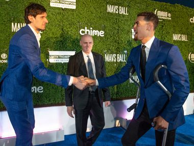 Mavs players Boban Marjanovic and Dwight Powell greet each other as head coach Rick Carlisle looks on on the blue carpet prior to the Mavs Ball at Million Air in Addison, Texas on March 7, 2020.