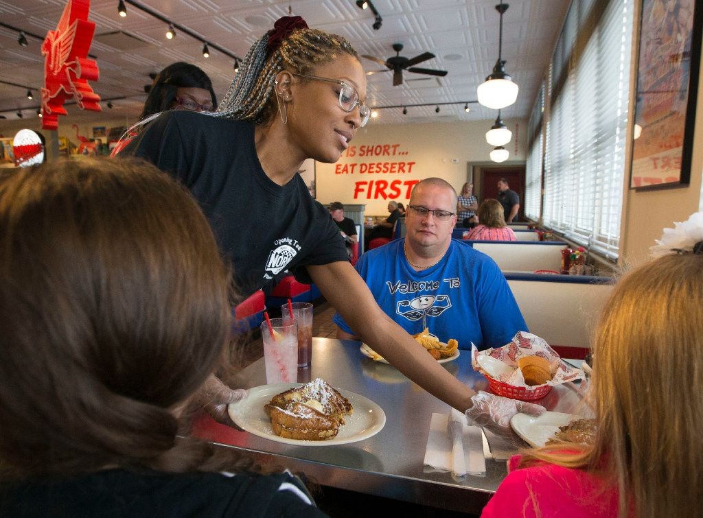 Waitress Morgan Butler delivers food to a table during the pre-opening weekend, at the new location of Norma's Cafe on 15th Street in Plano, Texas. (Ryan Michalesko/The Dallas Morning News)