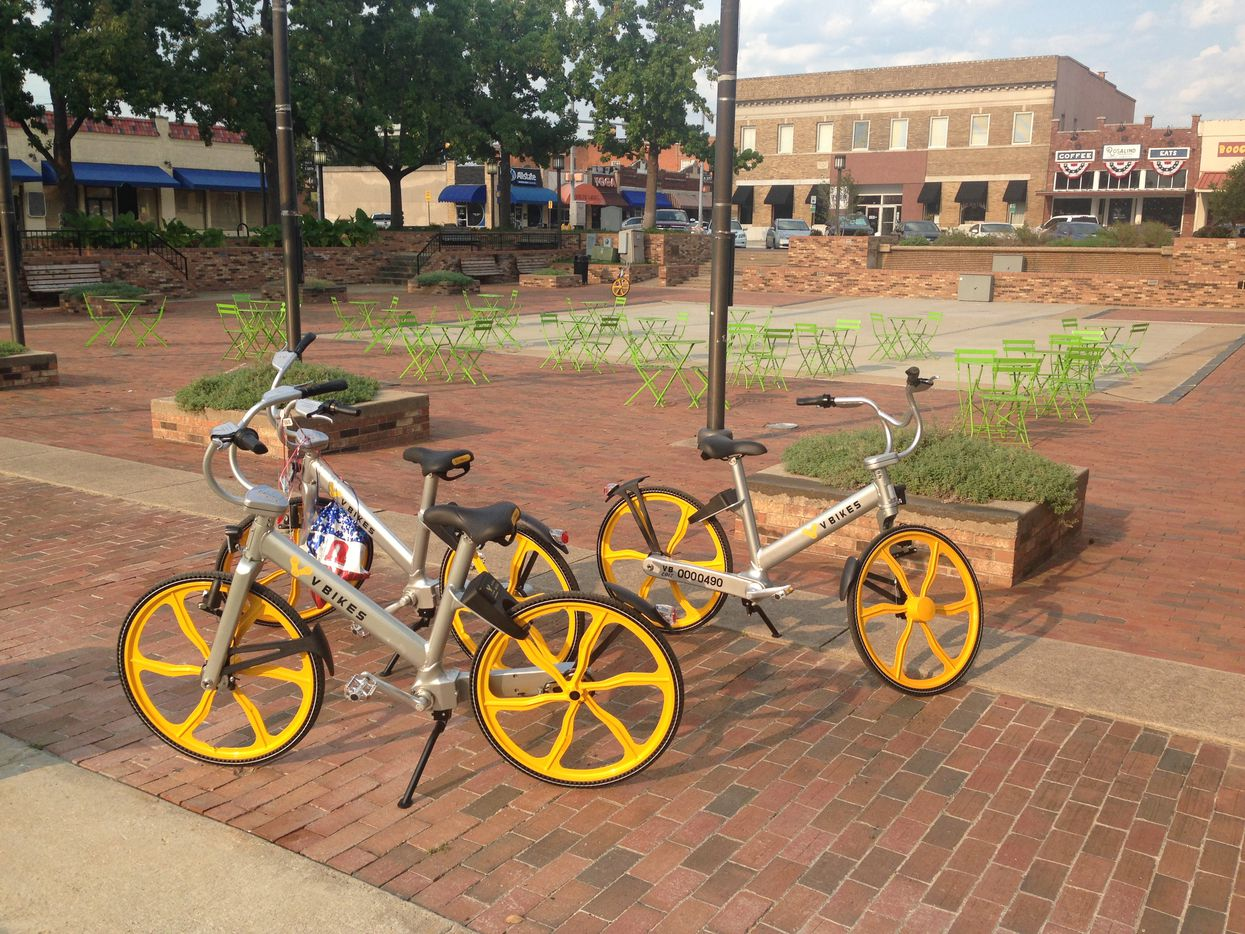 VBikes, one still bearing decorations from Garland's Labor Day parade, await their next user in the city's downtown square.