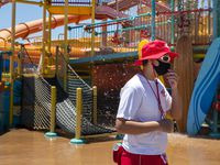 Lifeguard Michael Schmidt adjusts his face mask while monitoring water attractions at the Hawaiian Falls waterpark in Roanoke. Hawaiian Falls was one of the few water parks in North Texas to reopen Friday.