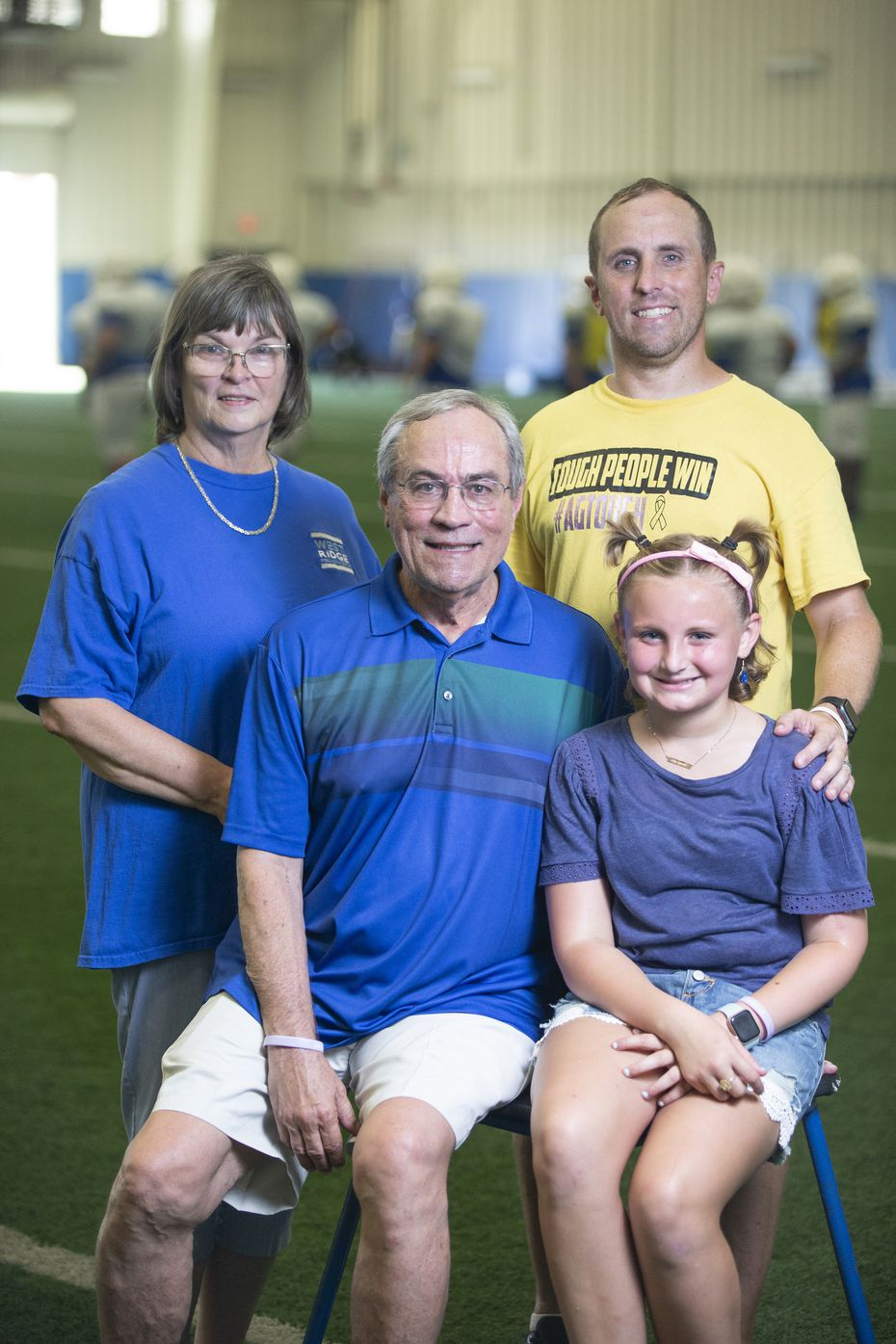 Former Grand Prairie ISD executive  director of athletics Gary Bartel, second from left, poses for a photo with his wife Pat, left, son, Eric and grand daughter Annabelle Grace, 11, at Grand Prairie High School's indoor practice facility, Wednesday, August 11, 2021. Annabelle Grace had bone cancer, now in remission, and has served as an inspiration for Gary who was on a ventilator for 103 days battling COVID-19. (Brandon Wade/Special Contributor)