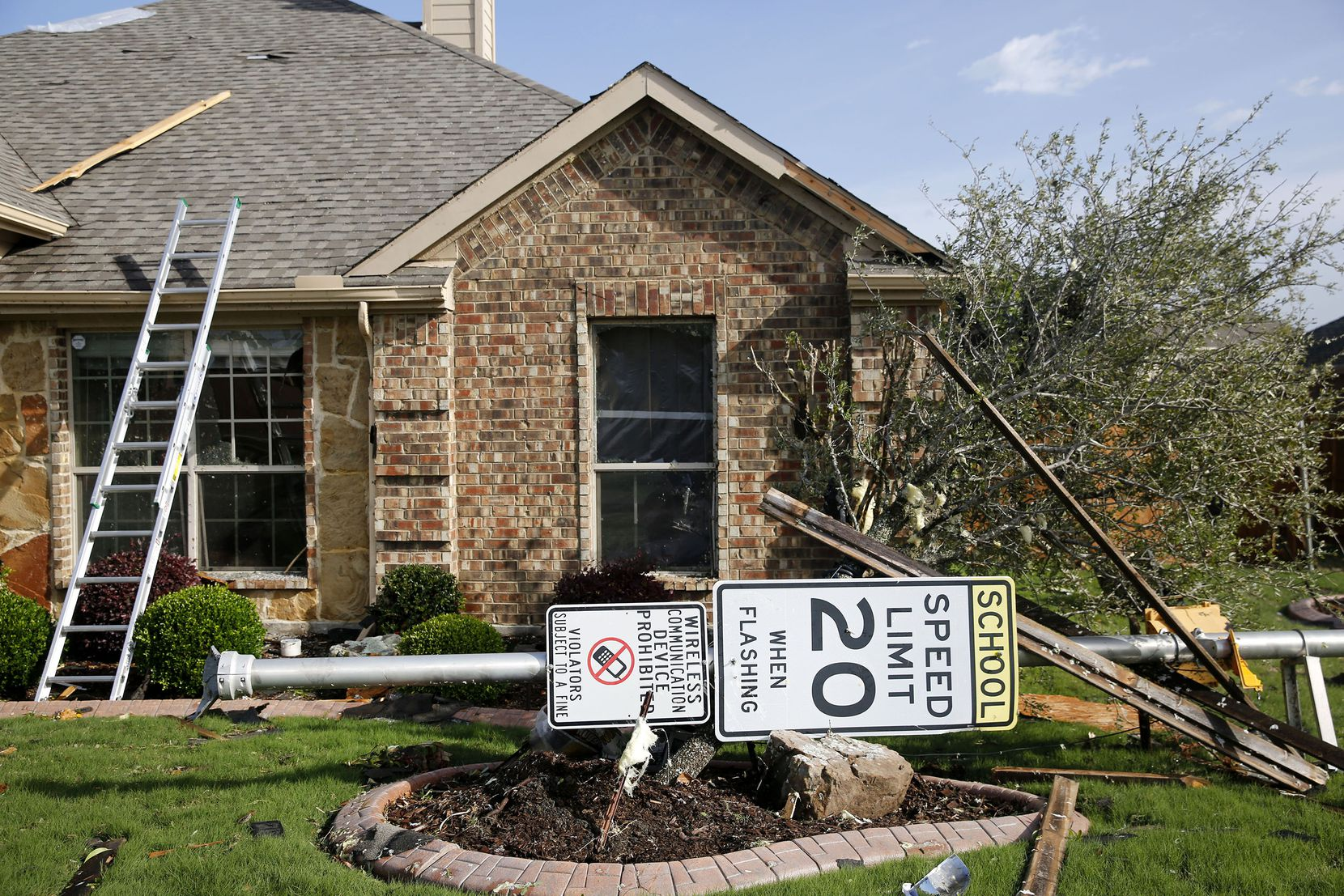 A sign lays in the yard of a home along Tannerson Drive following the storm in Rockwall. (Rose Baca/Staff Photographer)