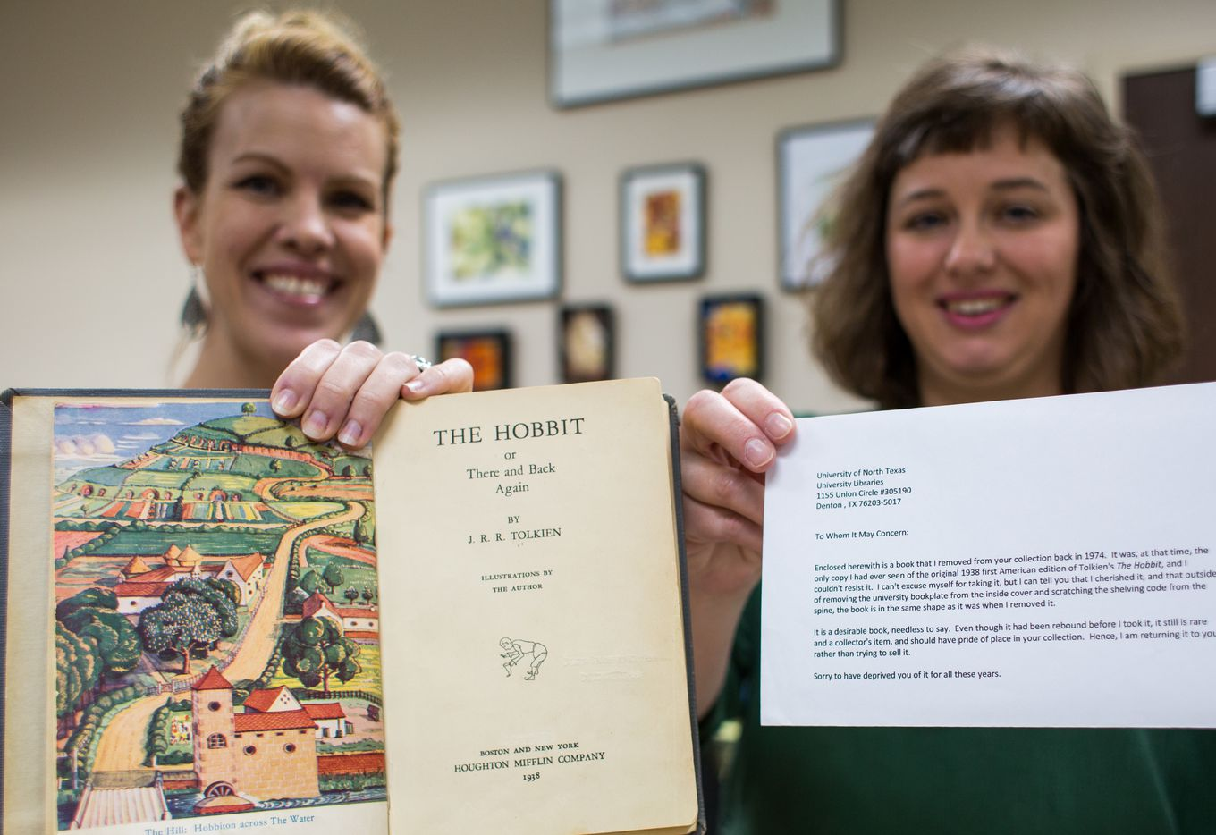 """UNT librarians Laurel Crawford and Morgan Gieringer hold the first edition 1938 copy of """"The Hobbit"""" by J.R.R. Tolkien and the anonymous letter that accompanied it."""