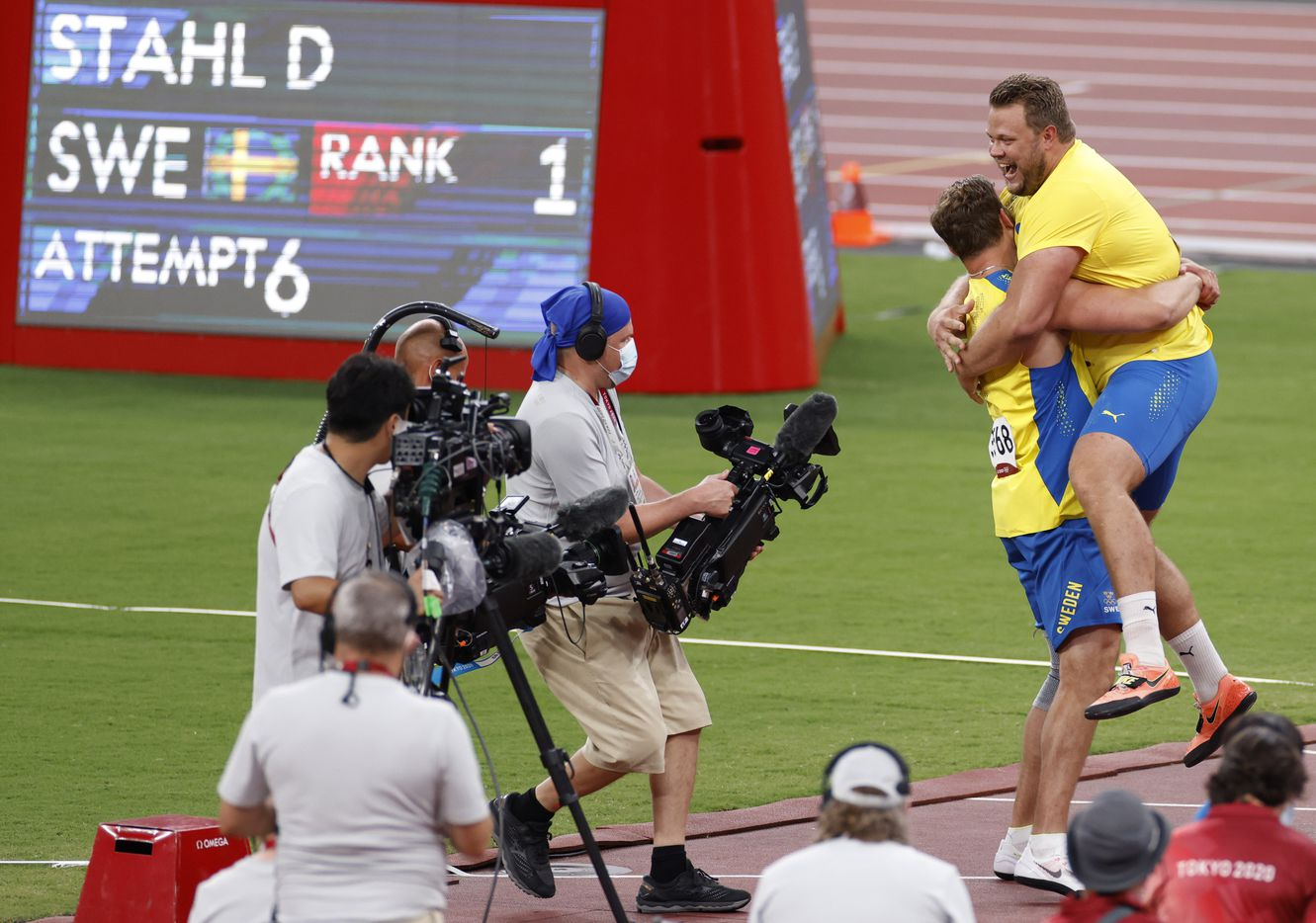 Sweden's Daniel Stahl is lifted up by Sweden's Simon Pettersson after the two took first and second place in the men's discus throw final during the postponed 2020 Tokyo Olympics at Olympic Stadium, on Saturday, July 31, 2021, in Tokyo, Japan. Stahl earned a gold medal with a throw of 68.90 meters and Peterson earned silver with a throw of 67.39 meters. (Vernon Bryant/The Dallas Morning News)