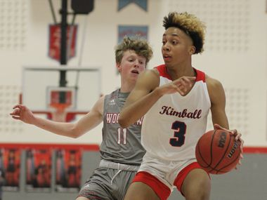 Kimball's Chauncey Gibson (3) drives inside as Woodrow Wilson's Adam Kirby defends during the second half of Kimball's 80-67 first-round playoff win at Skyline High School on Saturday. (Steve Hamm/Special Contributor)