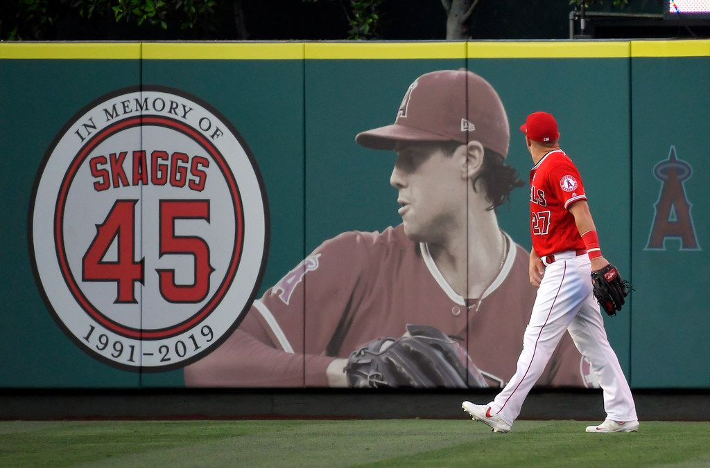 Los Angeles Angels center fielder Mike Trout walks by a picture of Tyler Skaggs in center field before a July 2019 baseball game in Anaheim, Calif.