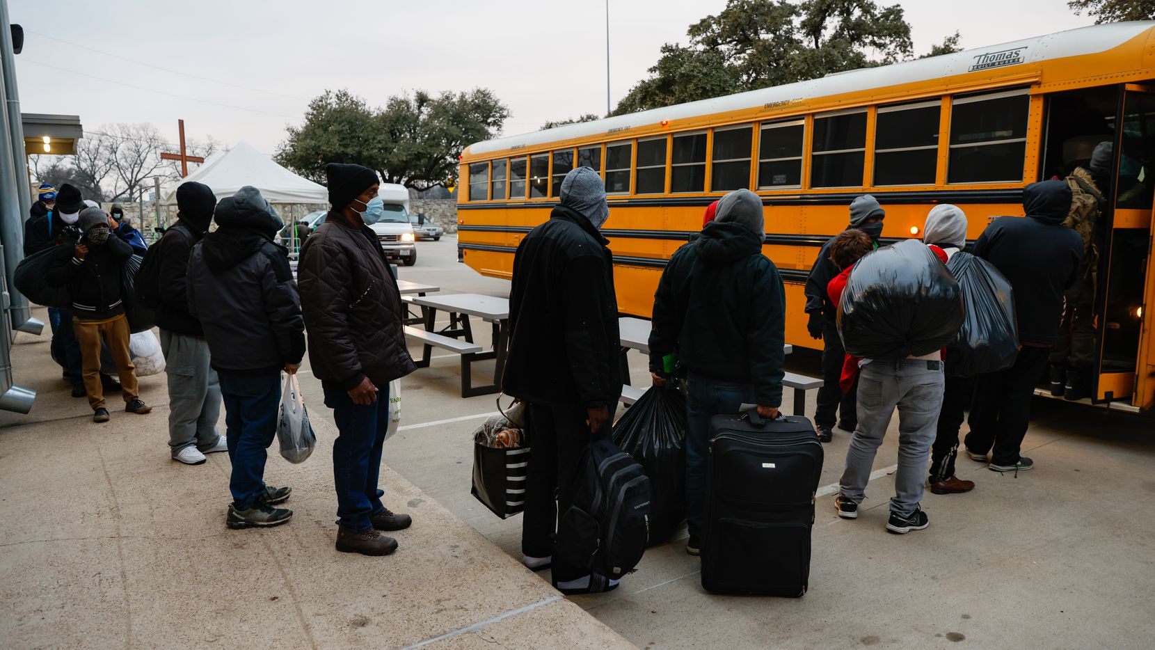 People load into a bus at OurCalling as they head to Kay Bailey Hutchison Convention Center in Dallas on Friday, Feb. 12, 2021. The City of Dallas opened the Convention Center to accommodate homeless individuals during the forecasted cold weather. (Juan Figueroa/ The Dallas Morning News)