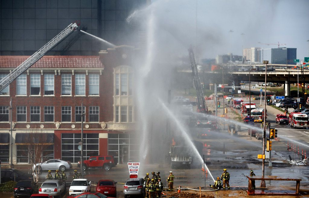 Dallas firefighters battle a fire caused by a ruptured gas line at a construction site along Cesar Chavez Boulevard at Main Street in downtown Dallas on Friday, March 10, 2017. A large drilling truck was engulfed with flames as aerial fire trucks poured on water.