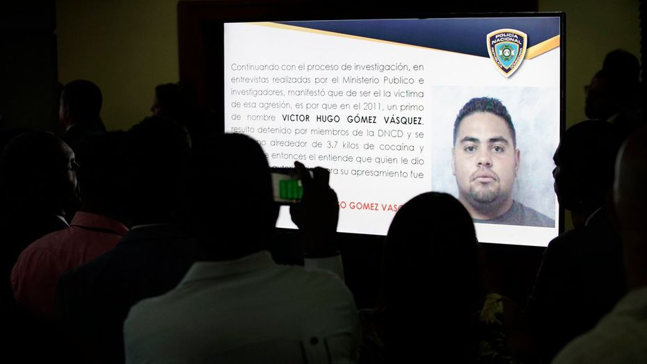 Journalists photograph a projected image of a man identified by authorities as Victor Hugo Gomez Vasquez, suspected mastermind of the attack that wounded former Boston Red Sox slugger David Ortiz in the Dominican Republic.