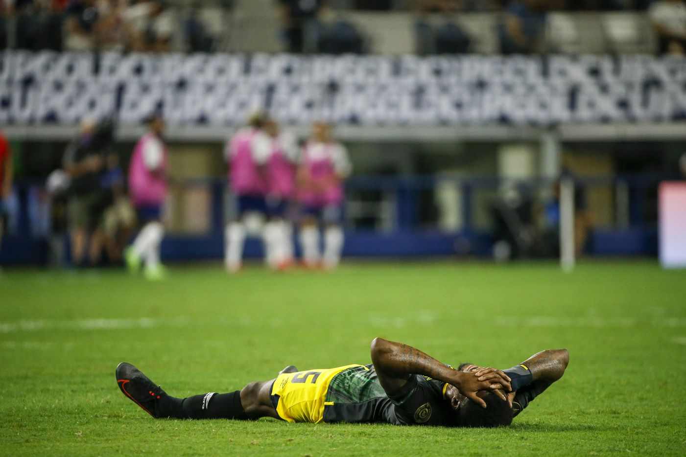 Jamaica defender Alvas Powell (5) lays on the ground injured during the first half of a CONCACAF Gold Cup quarterfinal soccer match against USA at AT&T Stadium on Sunday, July 25, 2021, in Arlington. (Elias Valverde II/The Dallas Morning News)