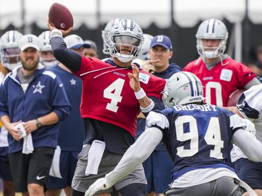 Dallas Cowboys quarterback Dak Prescott (4) throws a pass under pressure from defensive end Randy Gregory (94) during a practice at training camp on Sunday, July 25, 2021, in Oxnard, Calif.