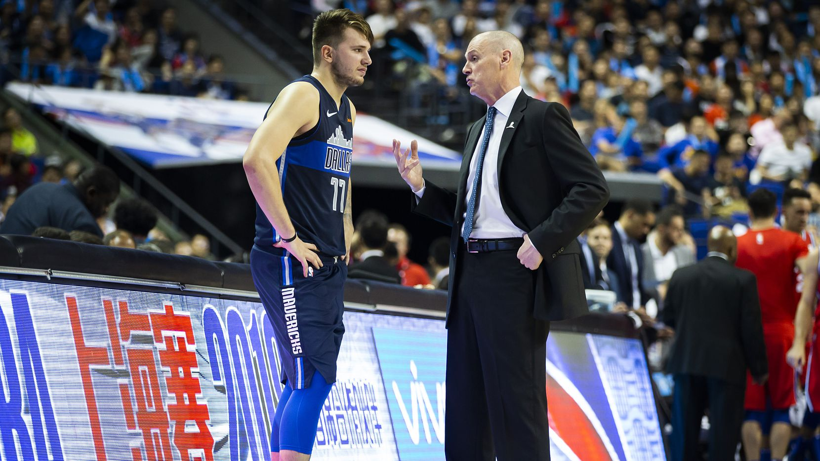 Dallas Mavericks guard Luka Doncic (77) talks with head coach Rick Carlisle before checking into the game after a timeout during the second half of an NBA China Games 2018 preseason basketball game against the Philadelphia 76ers at Mercedes-Benz Arena on Friday, Oct. 5, 2018, in Shanghai.