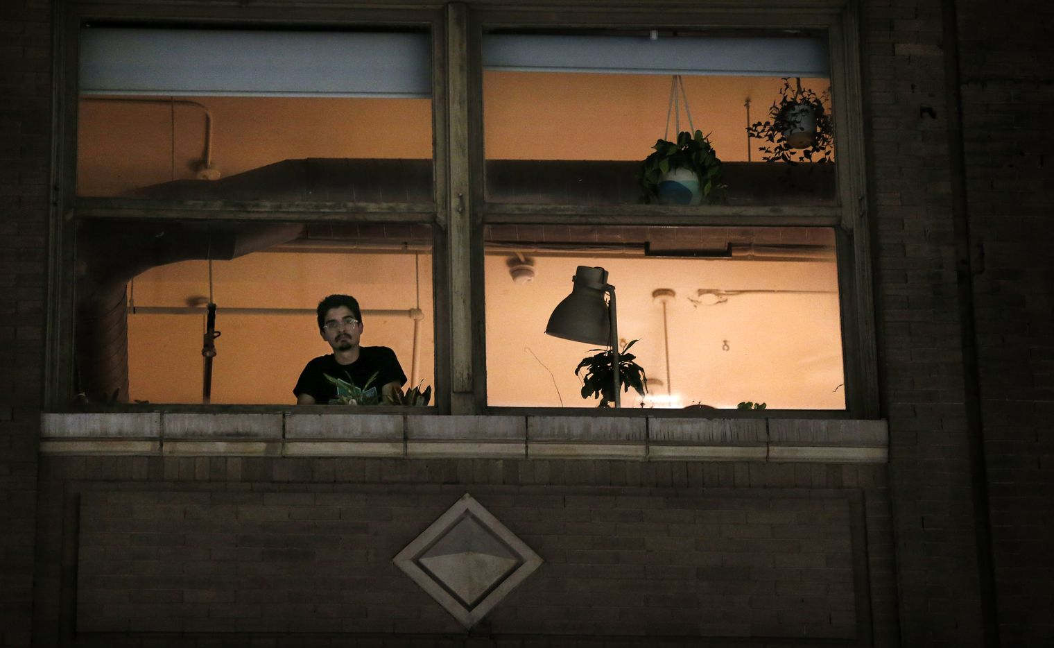 A man watches from his downtown Dallas apartment as Next Generation Action Network leads a parade of protestors down Elm St., Wednesday, September 23, 2020. The group supports Breonna Taylor who was killed by Louisville, Kentucky police.  A Kentucky grand jury brought no charges against the Louisville police for the killing of Taylor during a drug raid gone wrong. (Tom Fox/The Dallas Morning News) (Tom Fox/The Dallas Morning News)