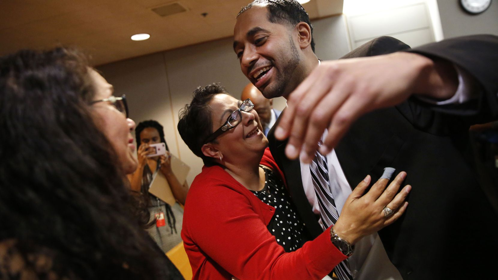 After hugging his aunt, Joanne Alonzo-Gloria, (center, in red) Quintin Lee Alonzo, (right) who was wrongfully convicted of the murder of Santos Gauna and sentenced to life in prison, reaches to hug his mother Julie Vazquez (far left, back to camera)  after being declared innocent during a hearing at the Frank Crowley Courts Building in Dallas on May 30, 2018.