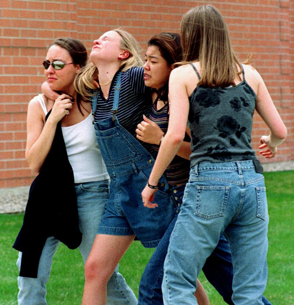 In this April 20, 1999 file photo, unidentified young women head to a library near Columbine High School where students and faculty members were evacuated after two gunmen went on a shooting rampage in the school in the southwest Denver suburb of Littleton, Colo.