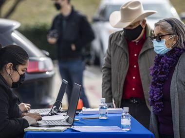 Noemi Gonzalez (izq), quien trabaja con la comisionada Elba Garcia, ayuda a los residentes de Oak Cliff Cleotilde y Salvador Ortega a registrarse para la vacuna contra covid-19 en un Pollo Campero en N. Cockrell Hill Road. El evento fue organizado por la activista Leslie Cannon.