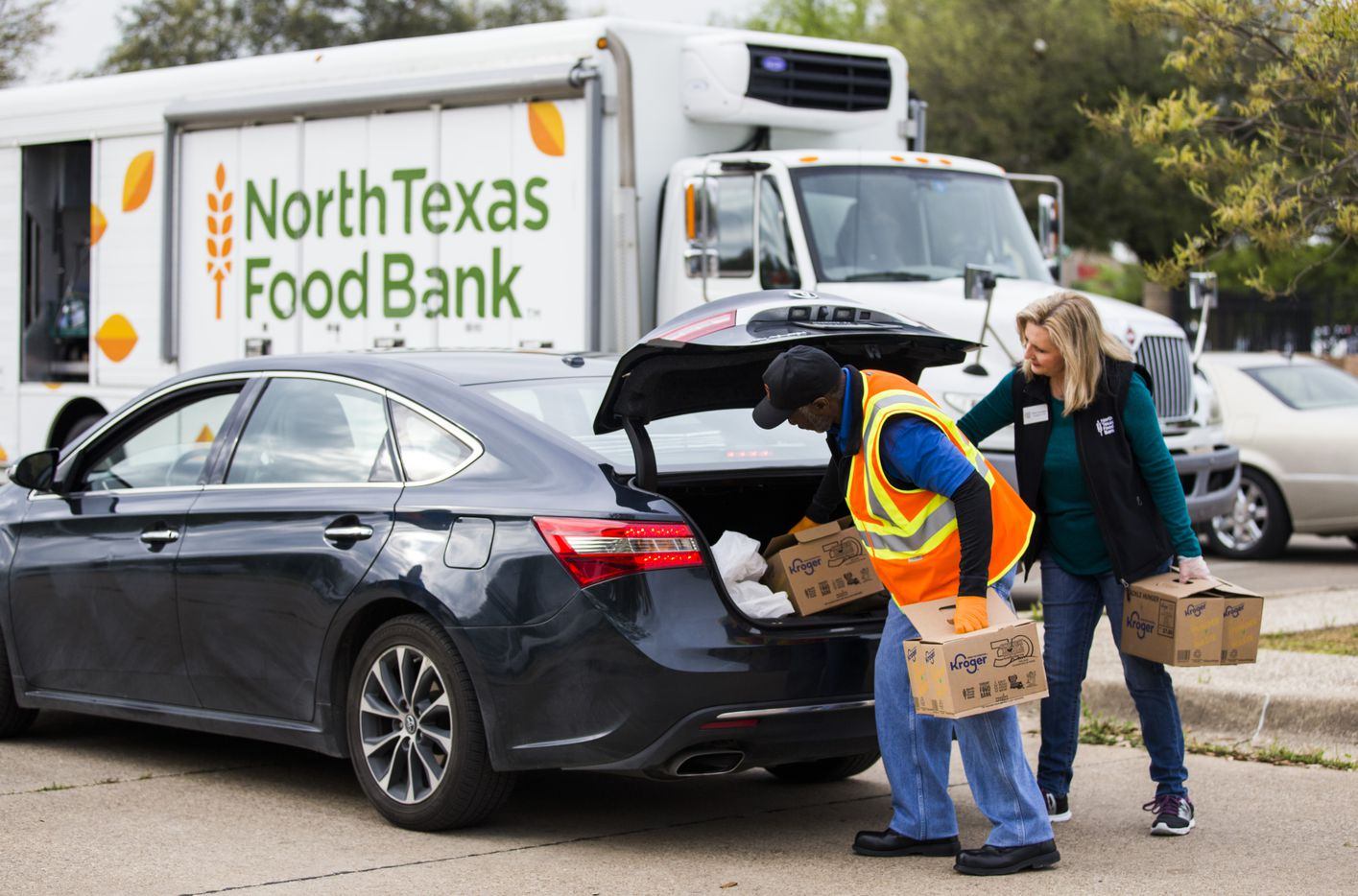 Volunteer Anthony Devers and North Texas Food Bank president and CEO Trisha Cunningham place boxes in one of the hundreds of cars lined up for food distribution.