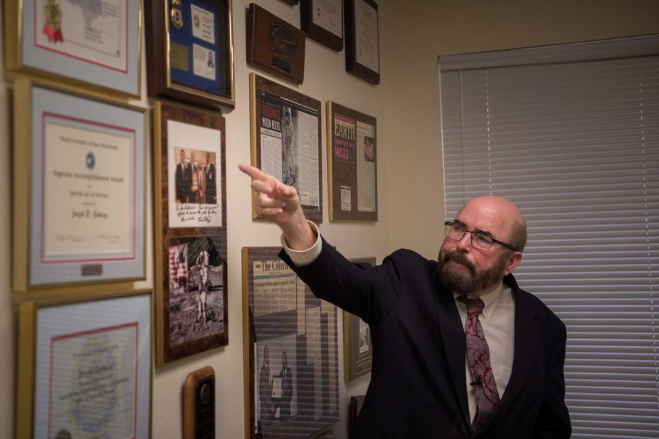 """Joseph Gutheinz, an attorney known as the """"Moon Rock Hunter,"""" points to plaques in his office in Friendswood, Texas."""