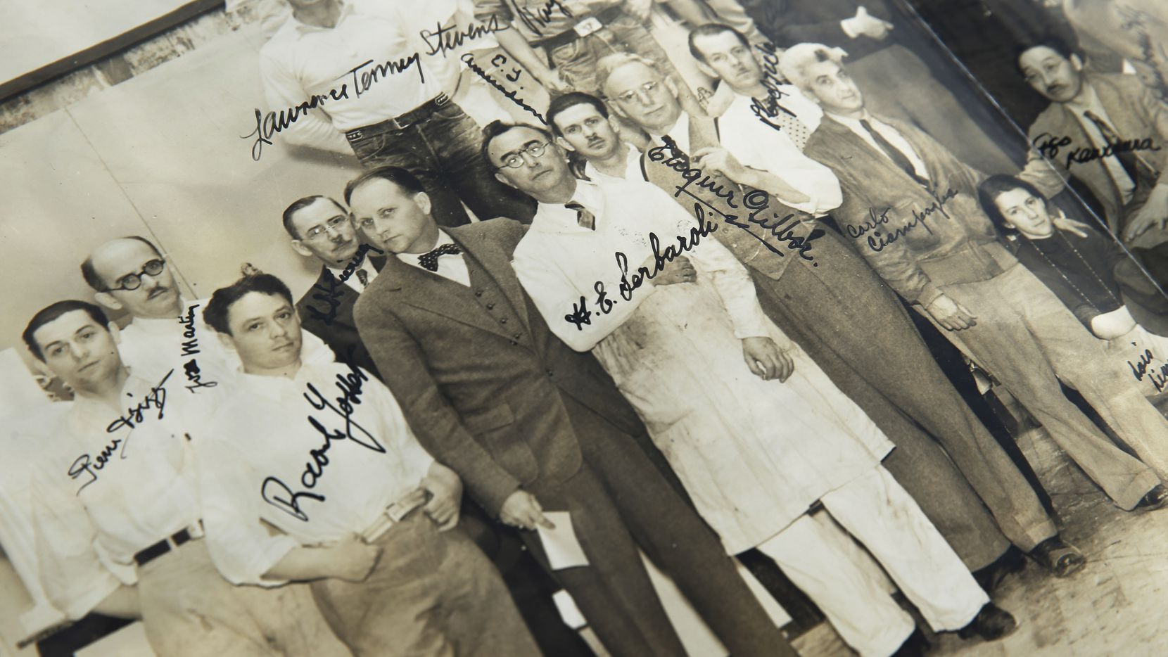 George L. Dahl (center in bowtie) poses with the men and women who helped design and construction the Fair Park campus for the 1936 Texas Centennial Exposition. This autographed photos is among the important keepsakes Adrienne Faulkner keeps in the Dahl archives.