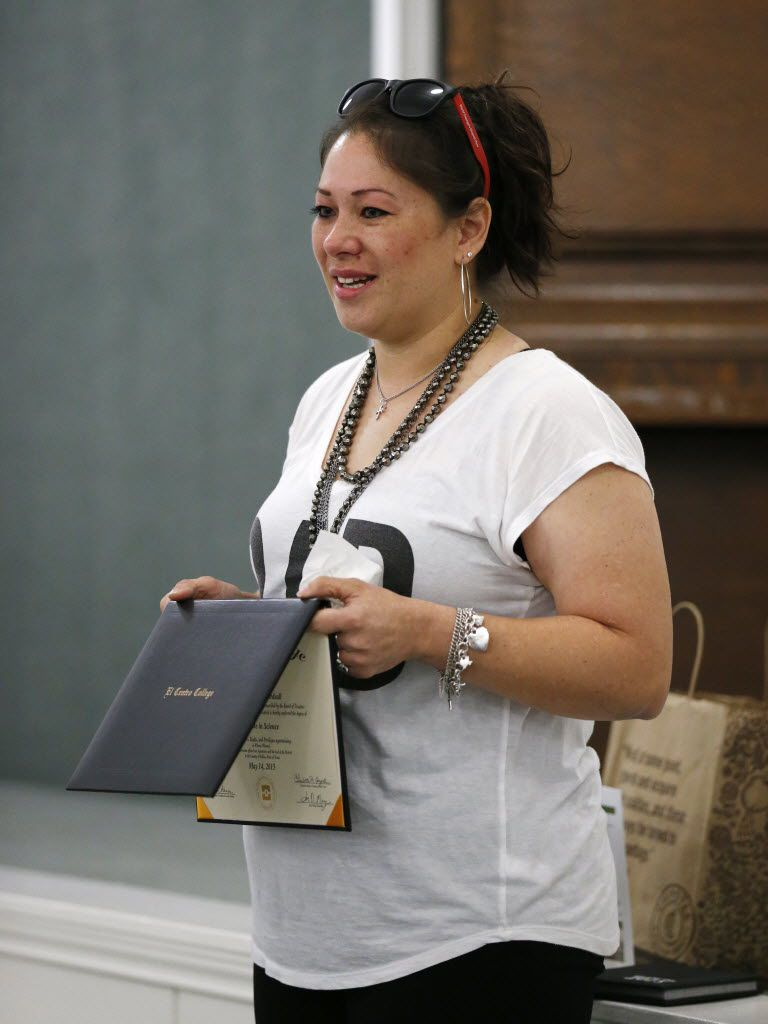 Wendy Birdsall, 41, holds up her diploma from El Centro College while talking to Celanese employee volunteers at Nexus Recovery Center in Dallas on Sept. 25, 2015. Birdsall. Birdsall was homeless at age 15 and had an on-an-off relationship with drugs in her early years. Now she splits her time between a daytime job and classes at SMU. (Rose Baca/The Dallas Morning News)
