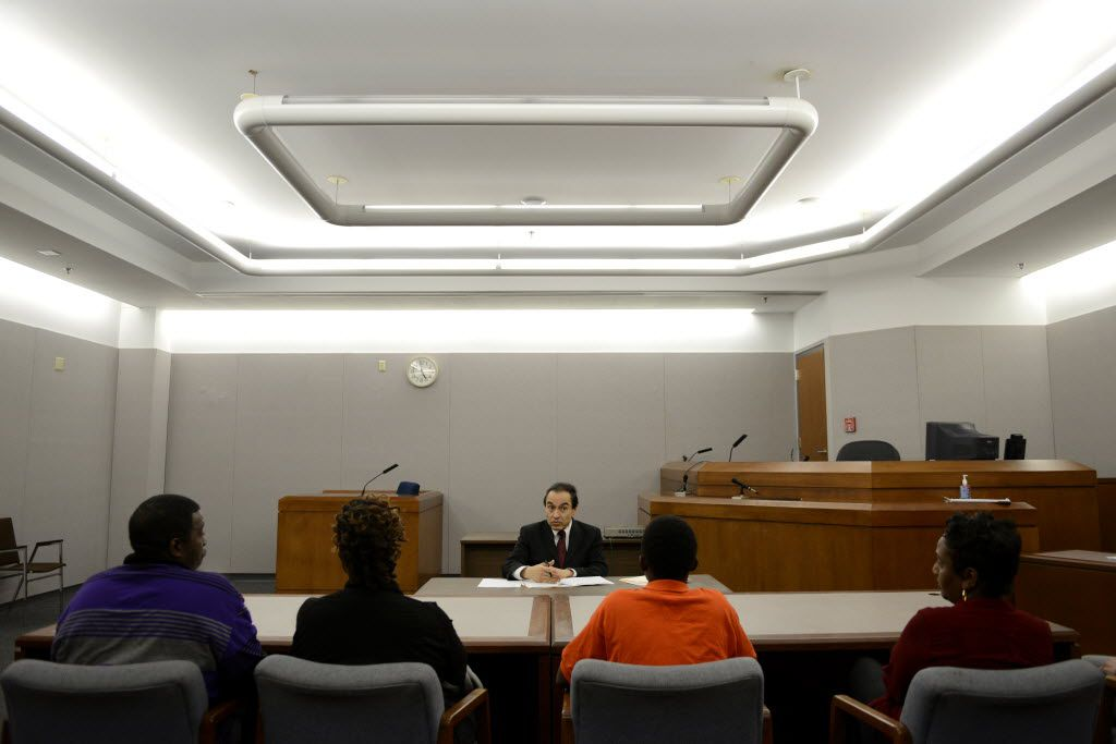 Judge Robert Herrera speaks to a boy, seated with his family and probation officer, who is enrolled in the diversionary program in the mental health court at the Henry Wade Juvenile Justice Center in Dallas on Feb. 10, 2015.