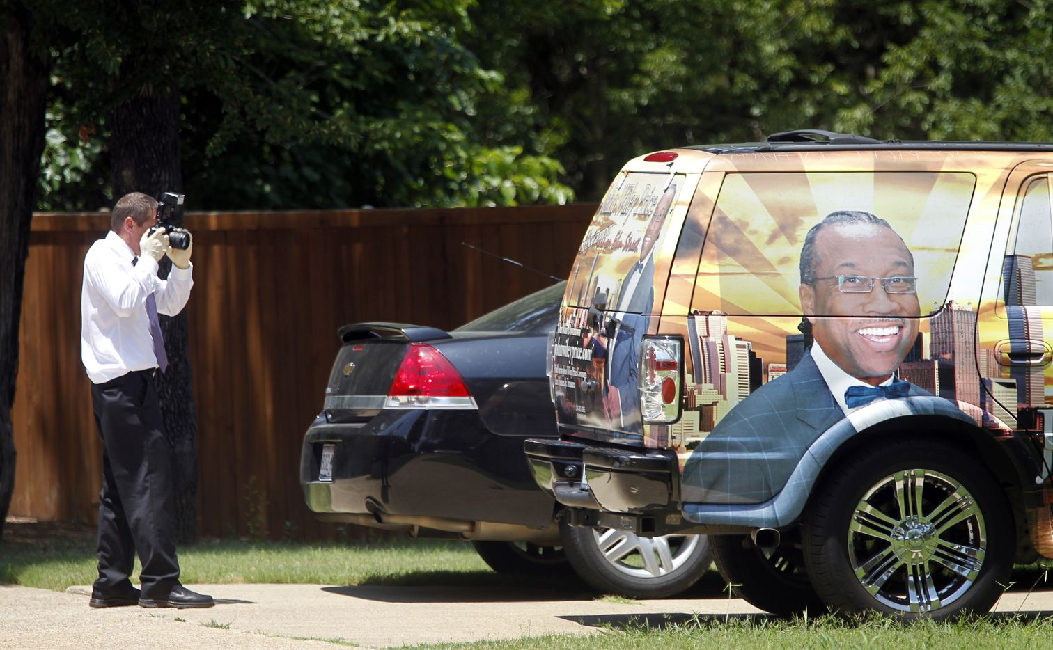 A law enforcement agent photographs a vehicle outside the DeSoto, Texas home of Dapheny Fain, the top assistant to Dallas County Commissioner John Wiley Price, in June 2011, as the FBI executed federal search warrants on Price's home and office, and those of key associates.